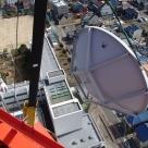 大型クレーンを用い鉄塔にパラボラアンテナを設置する状況